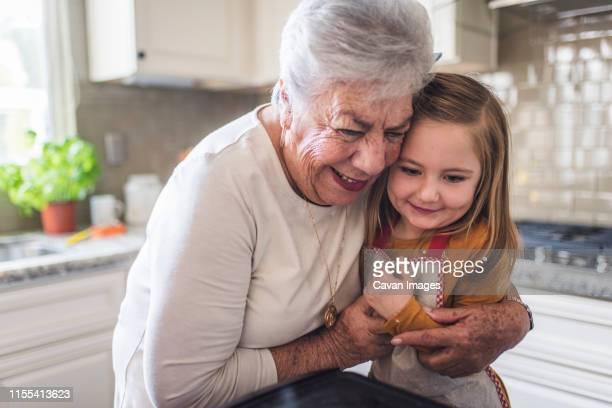 close up of great grandmother hugging great granddaughter - 家族の集まり ストックフォトと画像