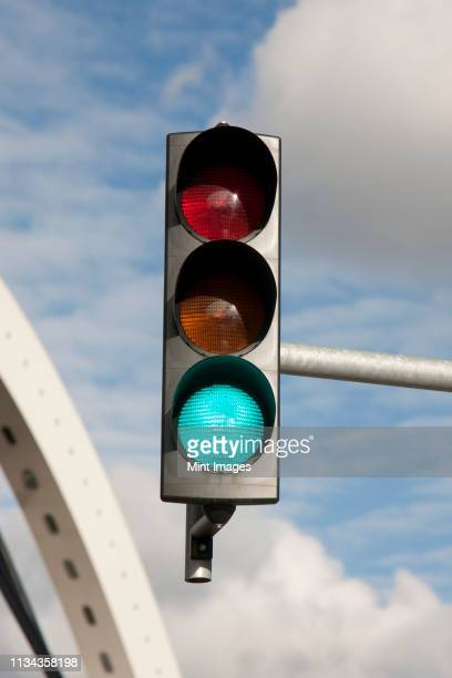 close up of green illuminated on traffic light - stoplight stock pictures, royalty-free photos & images