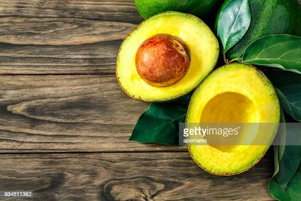 close up of green ripe avocados with leaves with copy space on board - ripe stock pictures, royalty-free photos & images