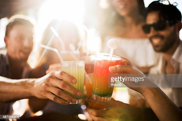 Primer plano de grupo de amigos con cócteles brindis.