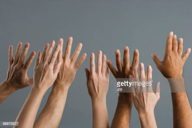 close up of group of hands raised - arms raised stock pictures, royalty-free photos & images