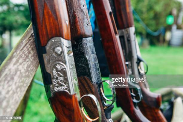close up of group of shotguns in a rack. - shooting crime stock pictures, royalty-free photos & images