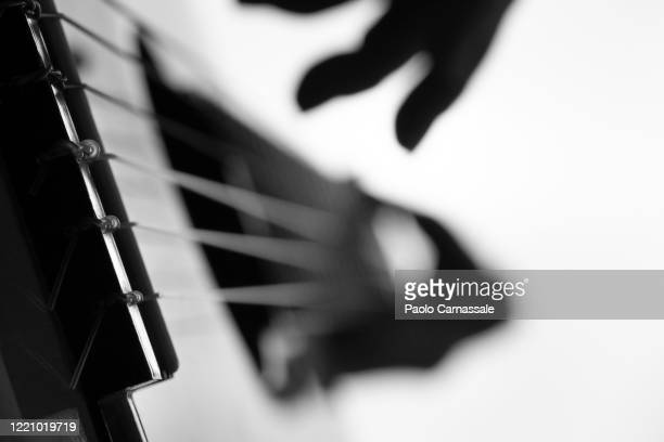 close up of guitar bridge with defocused fingers on white background - acoustic guitar stock pictures, royalty-free photos & images