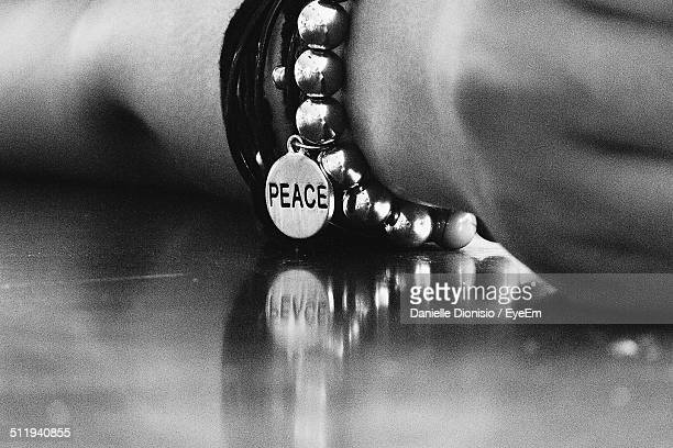 Close up of hand and bracelet with word peace on small pendant
