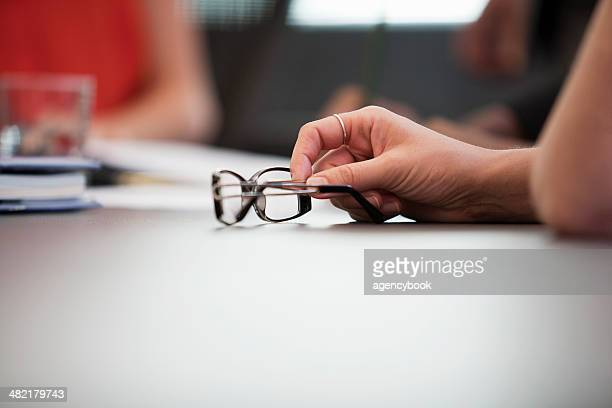 Close up of hand and spectacles at meeting