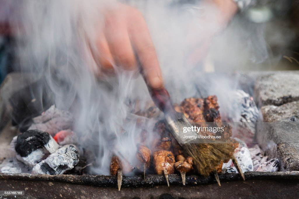 Close up of hand brushing meat on grille : Foto stock