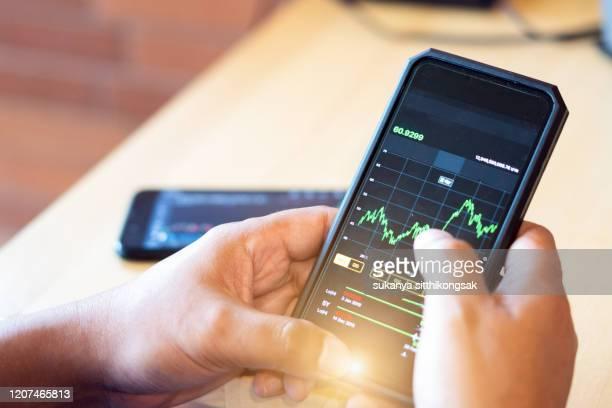 close up of hand businessman checking stock market data on mobile phone. - commerciële activiteit stockfoto's en -beelden