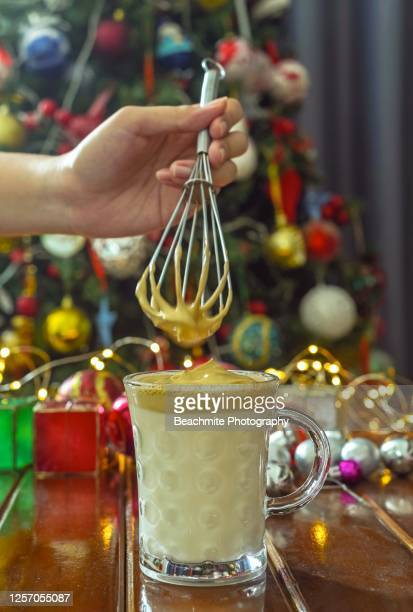 close up of hand holding an egg whisk preparing dalgona coffee - dalgona stock pictures, royalty-free photos & images