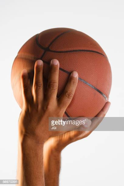 close up of hand holding basketball in air - making a basket scoring stock photos and pictures