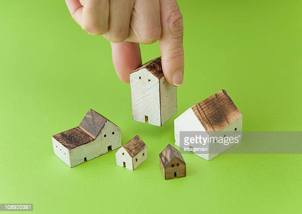 Close up of hand holding miniature houses