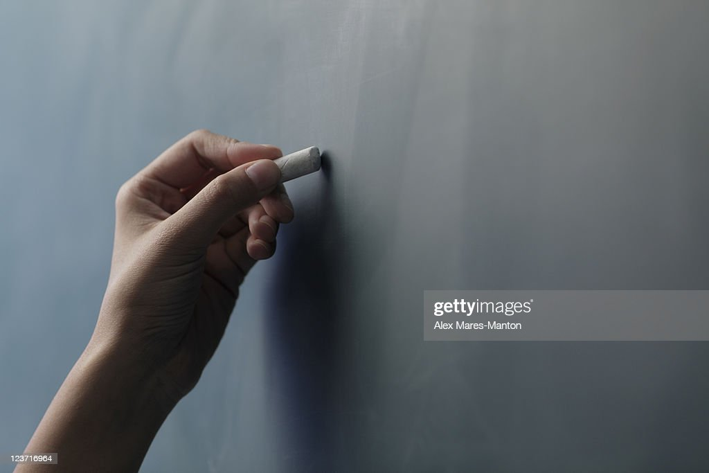 Close up of hand holding piece of chalk on chalkboard : Photo