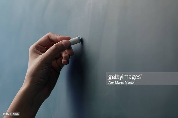 Close up of hand holding piece of chalk on chalkboard