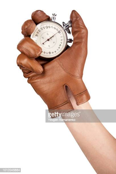 close up of hand holding stopwatch on white background - leather glove stock pictures, royalty-free photos & images