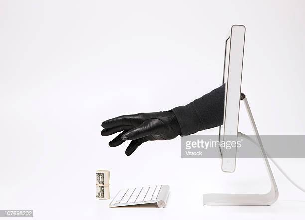 Close up of hand in black glove emerging through monitor