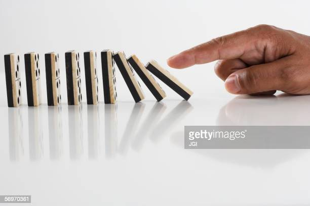 Close up of hand knocking dominos over