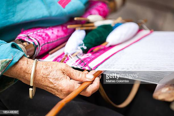 Close up of hand of old woman weaving