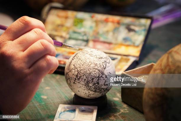 Close up of hand painting globe