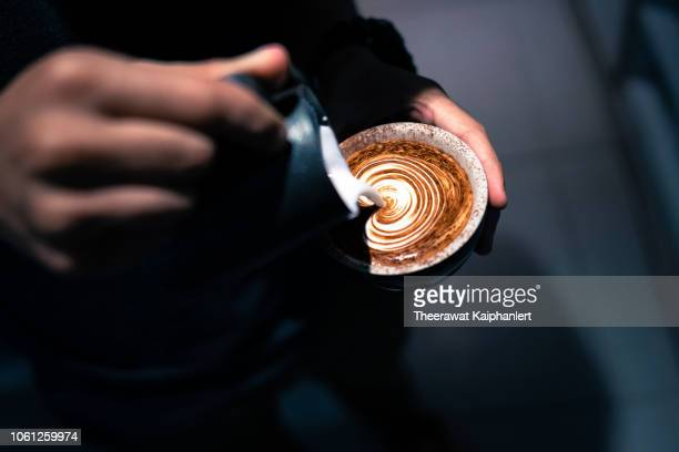 close up of hand pouring coffee latte art - coffee stock pictures, royalty-free photos & images