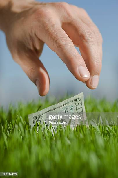 Close up of hand reaching for twenty dollar bill