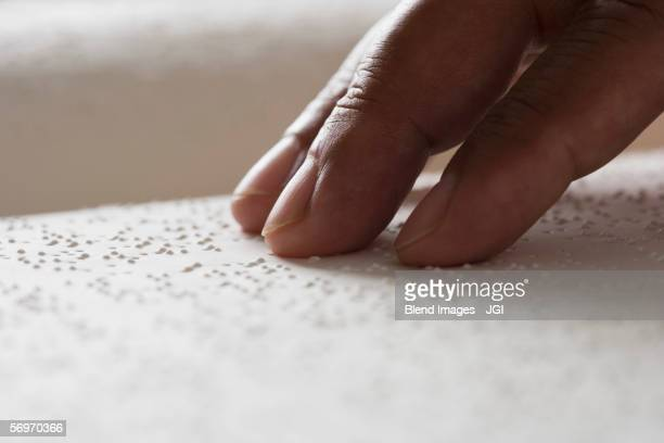 Close up of hand reading Braille