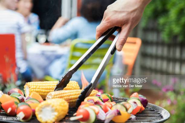 Close up of hand turning corn on the barbecue, using servingtongs.