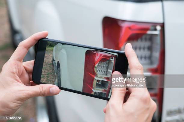 close up of hand woman take photo shattered car lights by smartphone. - damaged stock pictures, royalty-free photos & images