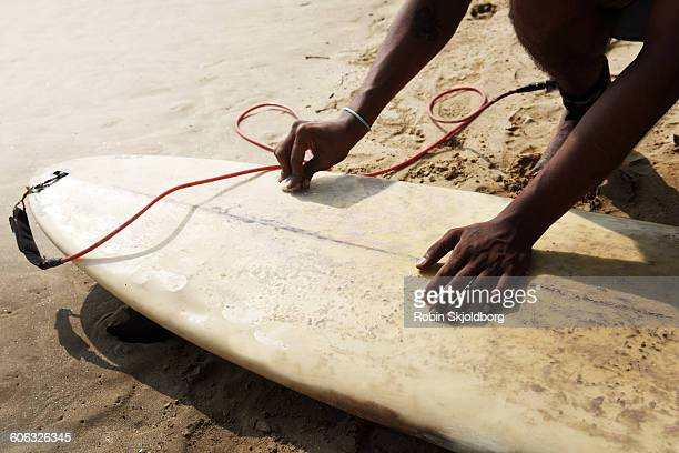 Close up of hands applying wax on surfboard