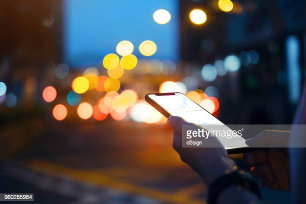 close up of hands checking financial trading data on smartphone in city street at night - wireless technology stock pictures, royalty-free photos & images