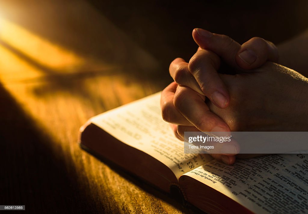 Close up of hands clasped on open Bible : Stock Photo