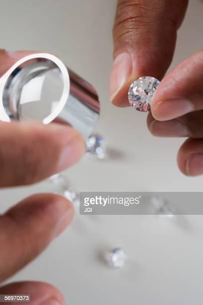 Close up of hands examining diamonds