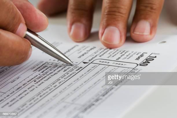 close up of hands filling in tax form - parte del cuerpo humano fotografías e imágenes de stock
