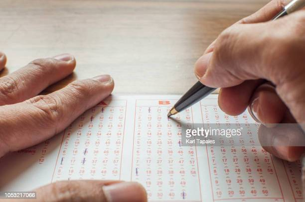 close up of hands filling up a lottery ticket form - 宝くじ ストックフォトと画像