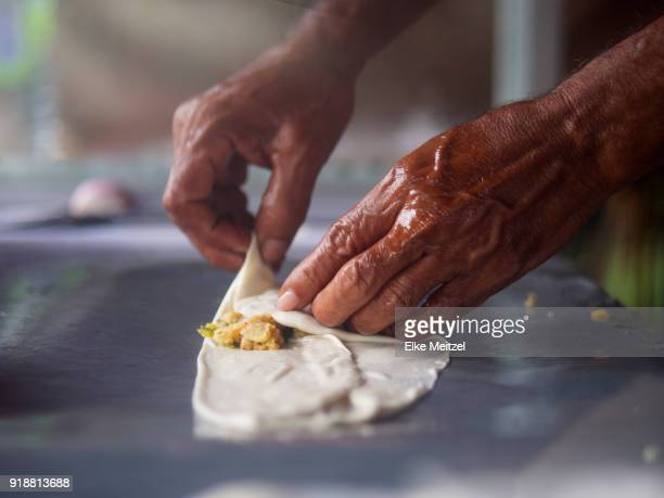 close up of hands folding a samosa