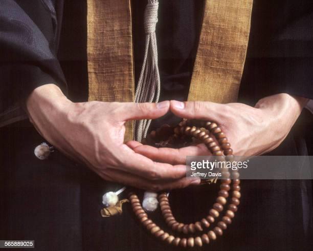close up of hands holding buddhist prayer beads - koyasan stock-fotos und bilder