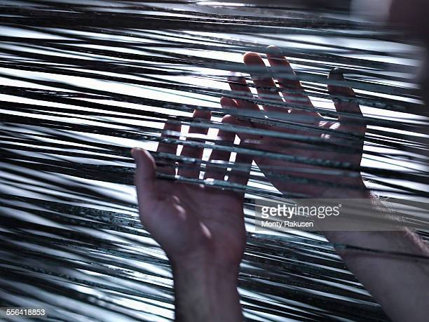 Close up of hands holding carbon fibre on loom in carbon fibre factory