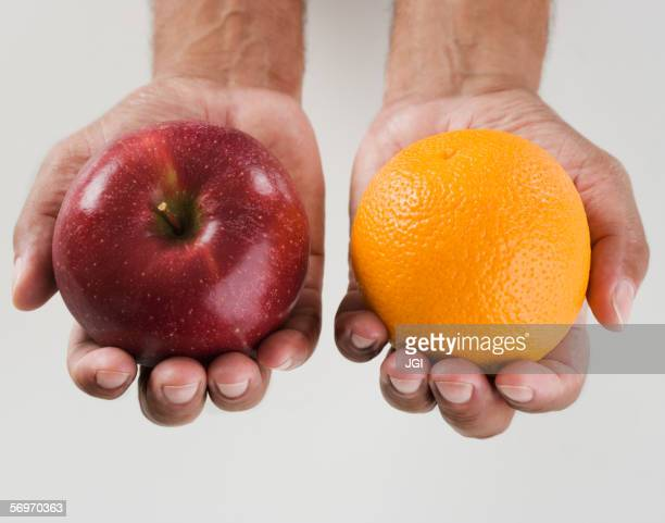 close up of hands holding two apples - comparison stock pictures, royalty-free photos & images