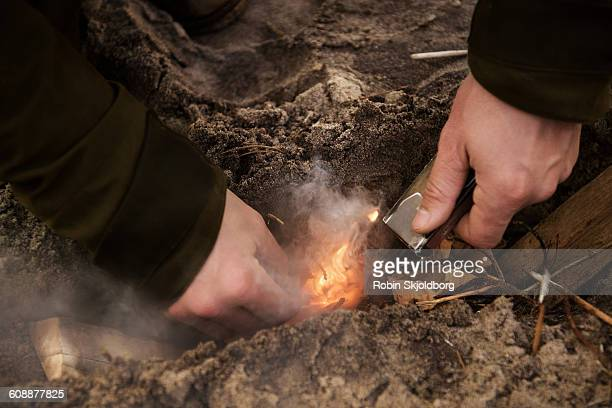 close up of hands lighting bombfire in sand - cigarette lighter stock pictures, royalty-free photos & images