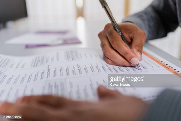 close up of hands man's completing absentee ballot - voting stock pictures, royalty-free photos & images