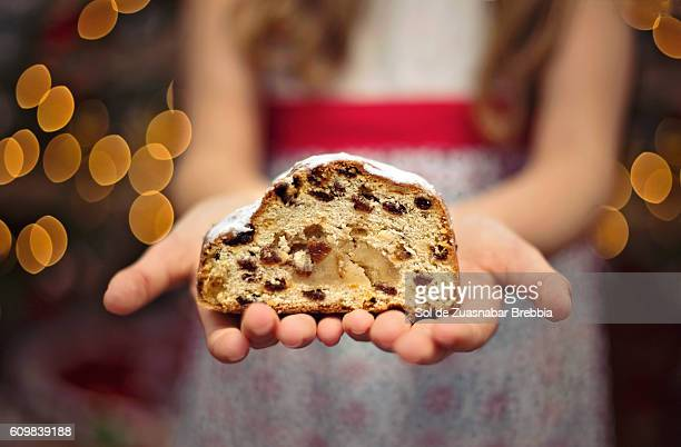 Close up of hands of a little girl holding a piece of Christmas sweet with the Christmas lights behind.