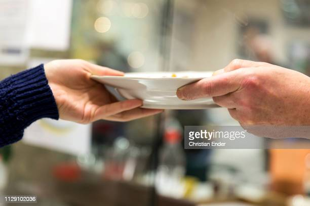 Close up of hands of a volunteer and a guest handing over a dish. Volunteers help on Christmas eve with lunch in Göttingen in the so called...