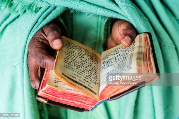 Close up of hands of priest holding Bible