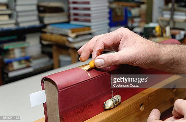 Close up of hands of senior male traditional bookbinder applying gold leaf to book spine