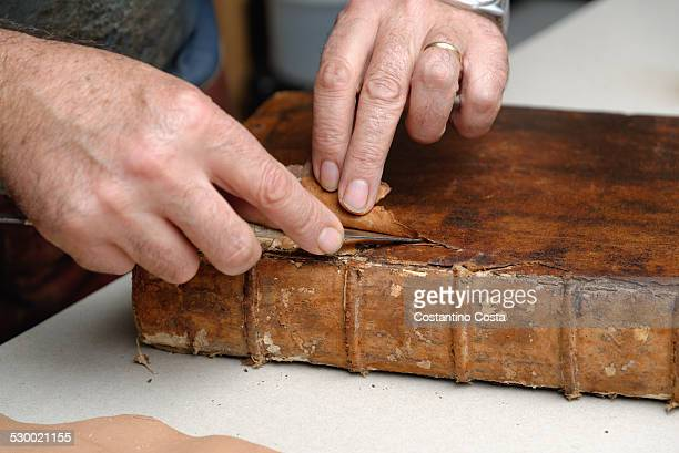 Close up of hands of senior male traditional bookbinder removing leather from book