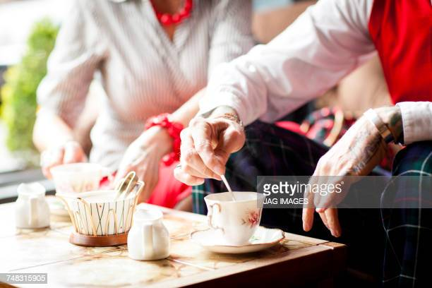 close up of hands of senior man stirring tea in vintage tea rooms - bournemouth england stock photos and pictures