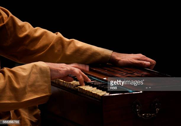 Close up of hands playing harmonium
