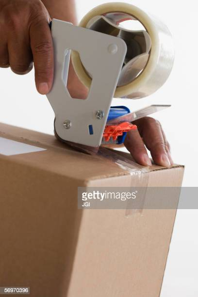 Close up of hands taping up box