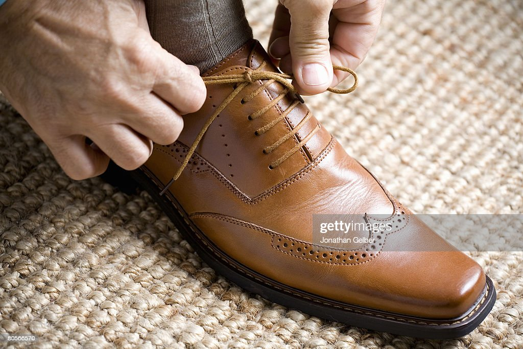 Close up of hands tying shoelace : Photo