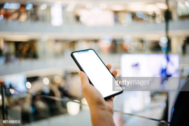 Close up of hands using smartphone in shopping mall