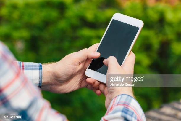 close up of hands using smartphone outdoors against fresh green background - phone message stock pictures, royalty-free photos & images