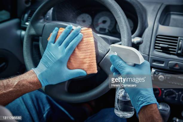 close up of hands with gloves applying spray alcohol and cleaning interior car - antiseptic wipe stock pictures, royalty-free photos & images
